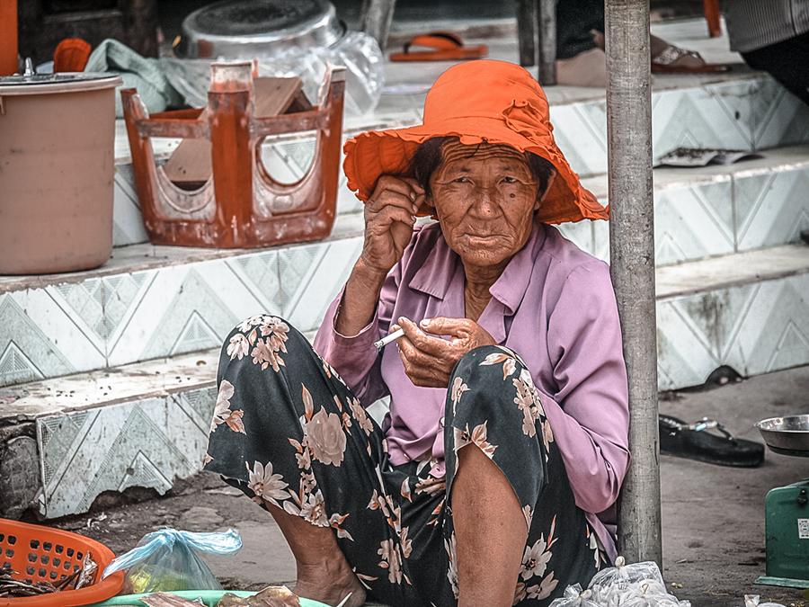 A seller at La Gi's fishing market enjoying a smoke